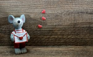 mouse figurine holding envelope and hearts