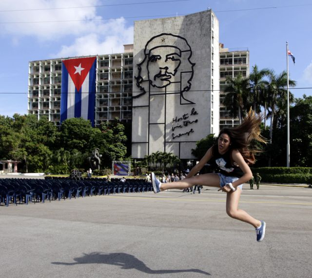 "Carolina, a tourist from Chile, jumps while having her picture taken by a friend before a tribute to revolutionary leader Che Guevara in front of the Cuban Interior Ministry (MININT) in Havana's Revolution Square October 8, 2013. Forty-six years after he was captured by soldiers in a Bolivian jungle and executed the next day, the Argentine-born Ernesto Guevara De La Serna, AKA, 'Che', is still a national hero in Cuba where he joined Fidel Castro in an armed uprising that ousted a U.S. backed dictator in 1959. Tuesday will be Guevara's 46th death anniversary. The words on the building read: ""Onward to victory, always""."